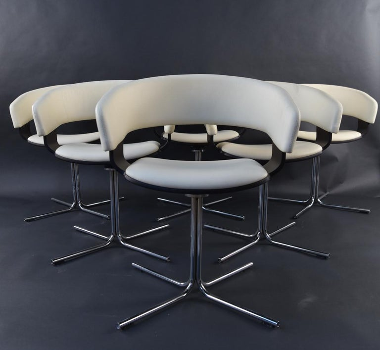 The 'Mollie' chair features soft cream leather, dark wood accents, and chrome swivel base.