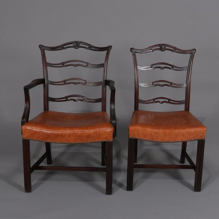 A set of 12 antique Chippendale style ribbon back dining chairs feature mahogany frames with laddered ribbon backs and upholstered seats, includes 2 arm and 10 side chairs, circa 1920.  Measures: Armless 36.5