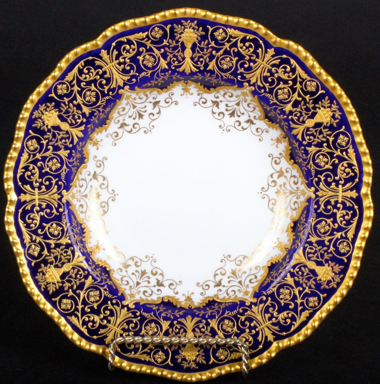 These 12 ornate soup plates are from the esteemed firm of Coalport, Shopshire, England. The soup plates feature wonderfully intricate raised-paste gold work of alternating ornaments of 2 different designs, one of a grand vase spewing meandering