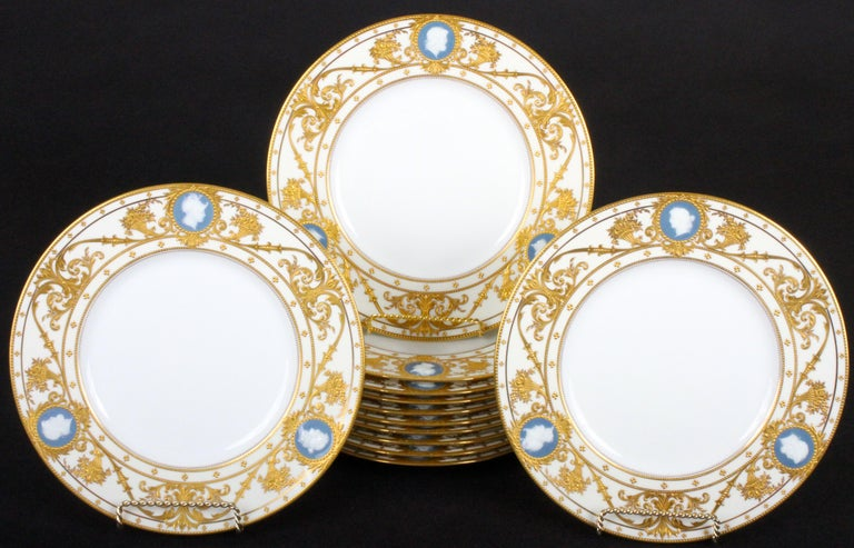 This pristine set of pate-sur-pate service, cabinet or dinner plates features reserves of classical cameo heads and heavy 22-karat raised paste gold gilding. The cameos are composed of white slip set on a blue background, they are ringed by gold