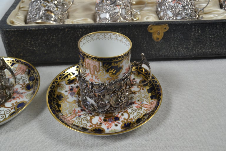 12-piece blue, white and multi color bone china Royal Crown Derby 3788 antique coffee service with ornate floral and geometric motif throughout, gilt trim and brand stamp at undersides. Includes 6 Royal Crown Derby flat cups, 6 Royal Crown Derby