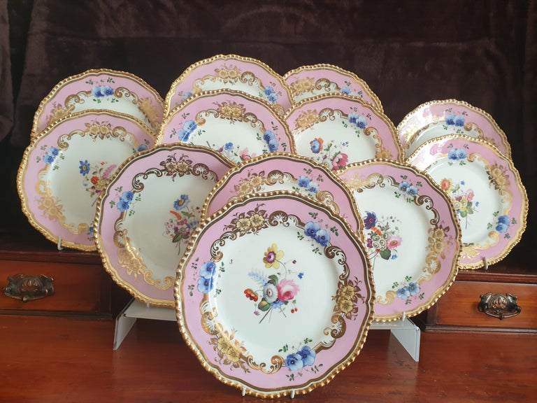 A Coalport set of 12 pink dessert plates all believed to be hand painted pieces by Steven Lawrence. In excellent condition, dates from the 1820's with 24k gold gilded rims.
