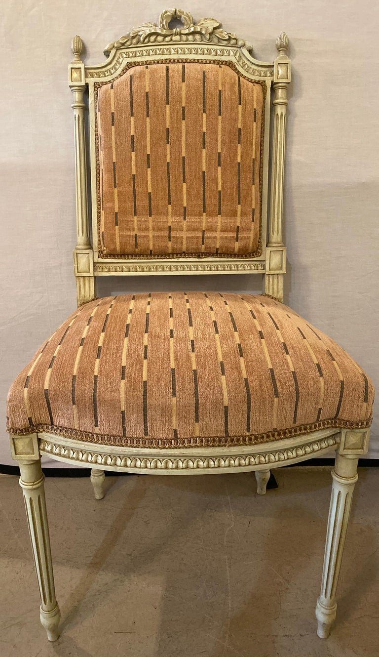 12 Swedish Louis XVI style dining / side chairs painted carved frames new fabric. Each stripped rose colored newly upholstered and refinished dining chair is finely carved with tapering legs supporting a square padded seat rest with carved apron.