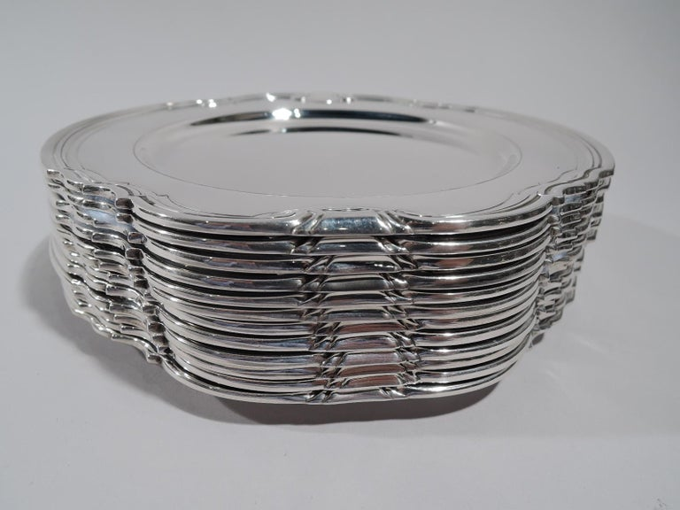 Set of 12 Castilian sterling silver bread and butter plates. Made by Tiffany & Co. in New York, circa 1929. Round with deep well. Shaped and molded rim with stylized volute scrolls. Super stylish in a less well-known Art Deco pattern. Fully marked