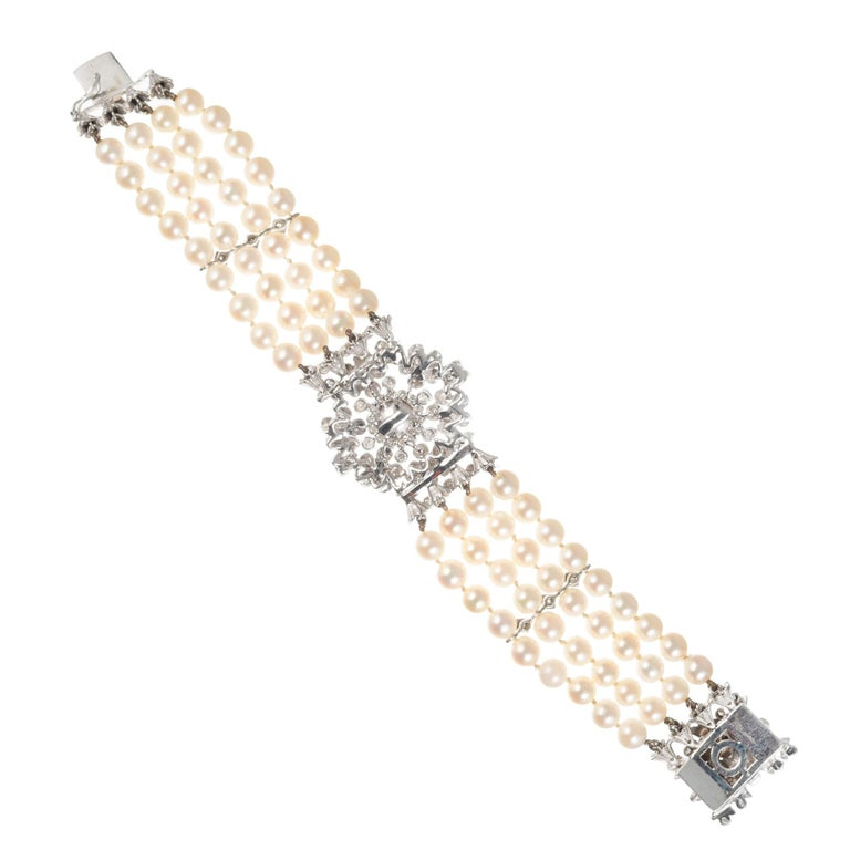 Vintage 1950's four row cultured pearl bracelet with a diamond and pearl center and a diamond and pearl catch. Diamond spacers and white gold case. 7 inches long.   72 cultured white with crème color pearls, 5.5mm 6 cultured white with crème color