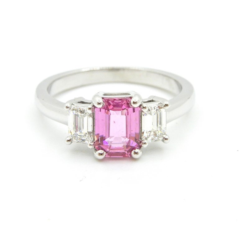This 1.21 Carat Emerald Cut Pink Sapphire and Diamond Engagement Ring is set in 18 carat white gold. The rounded band flows up to support a central 4 claw mount holding an emerald cut natural, no heat pink sapphire with 4 claw set emerald cut