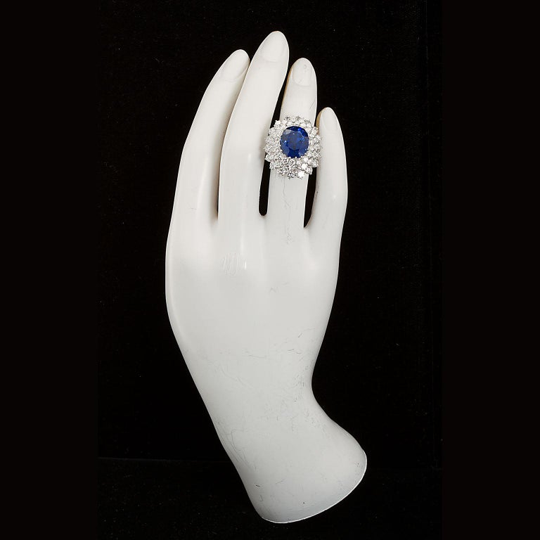 A Burmese Unheated deep transparent blue oval sapphire and diamond cluster ring.  Centering on an Oval shape 12.10 carat blue sapphire set in a round brilliant-cut diamond surround; estimated total diamond weight 5.25 carats; mounted in