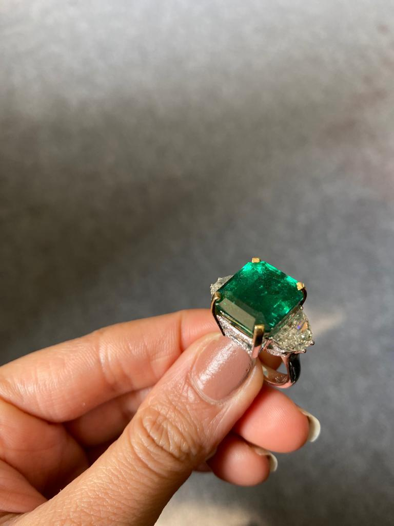 A statement three stone engagement ring, with a toip quality 12.17 carat transparent natural Zambian Emerald centre stone and 2 carat-each half-moon side stone diamonds. The emerald is of great lustre and has an ideal colour with very few minor