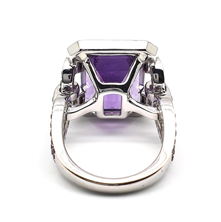 An eyecatching in colour splendid matching 18Krt White Gold ring occupied with 12.18ct an 8-angled cut Amethyst entourage, lilac-blue Corunds, 1.12ct, and 0.28ct brilliantly cut diamonds, colour W and clarity VVSi combined with pink Corunds