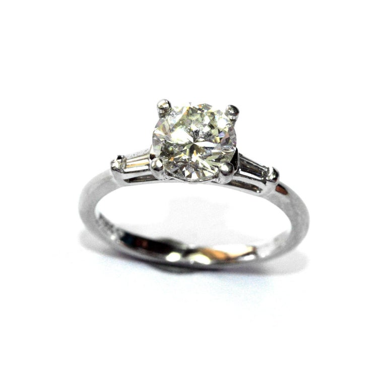 A 1.22ct diamond mounted in a platinum mount with tapered baguette diamonds in each shoulder. The diamond measures 6.7mm X 4.25mm  is J colour with an SI 2 clarity. There are 2 tapered baguette diamonds set in each shoulder weighing 06ct each. The