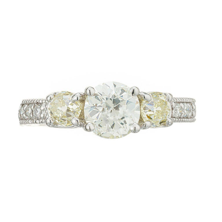 Diamond engagement ring. EGL Old European cut center diamond with 2 old European cut light yellow side diamonds in a 14k white gold Lucinda cross prong style setting with engraved sides and 6 diamond bead set on each side. Raised crowns and small