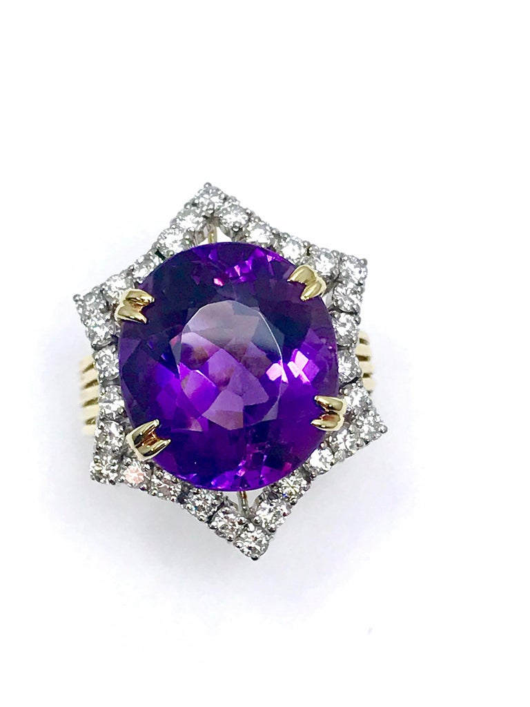 This is an extremely vibrant violet purple Amethyst and Diamond cocktail ring.  The 12.20 carat oval Amethyst is set with four double prongs, surrounded by a single row of inward curving diamonds.  The diamonds are round brilliant cuts weighing 1.10
