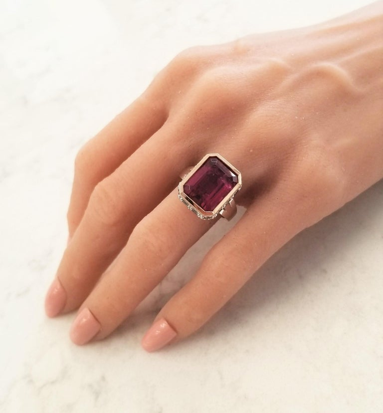 This ring raises the design bar! A 12.22 carat deep purplish-pink rubellite tourmaline is bezel set in the center in a rich rose gold and measures 15x11mm. The gem source is Brazil; its saturation is vivid; its transparency and luster are excellent.