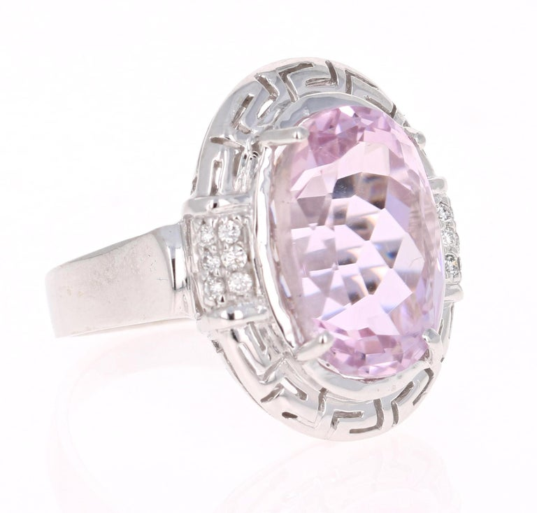 This stunning Art Deco - Inspired ring has a large 12.09 Carat Kunzite and is surrounded by 14 Round Cut Diamonds that weigh 0.14 carats.  The total carat weight of the ring is 12.23 carats. The design of this ring is so unique and totally art-deco