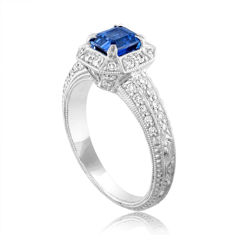 Beautiful Art Deco Revival Emerald Cut Milgrain Filigree Ring The ring is 18K White Gold The Center Stone is an Emerald Cut Blue Sapphire 1.24 Carats The Sapphire is Heated There are 0.60 Carats in Diamonds F/G VS/SI The ring is a size 6.75,
