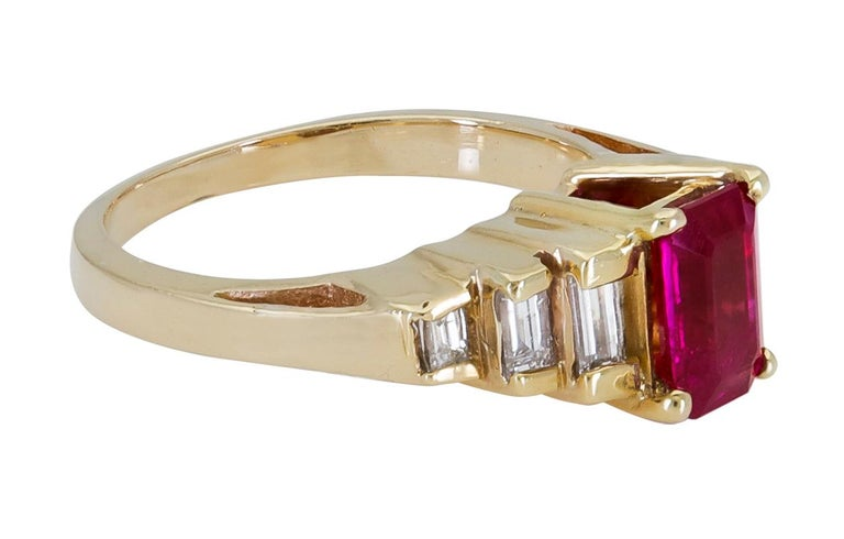 A magnificent engagement ring showcasing a 1.25 carat emerald cut red ruby. Flanking the center gemstone are three graduating baguette diamonds on either side. Made in 18k yellow gold.  Ruby weighs 1.25 carats. Diamonds weigh 0.20 carats total. Size