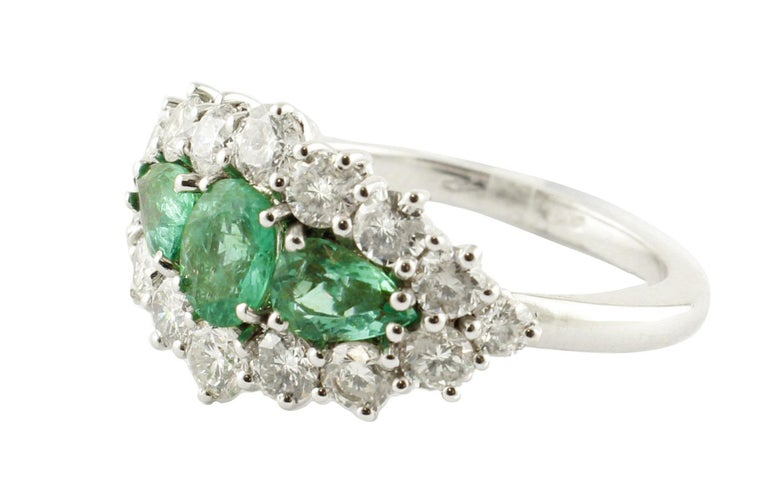 Shining ring in 14K white gold composed of 3 emeralds in the center (1.25 ct) ( 1 oval shape and 2 drop shape) surrounded all around by 1.72 ct of amazing white diamonds. Diamonds 1.72 ct  Emeralds 1.25 ct  Total Weight 6.20 g  R.F + hrue Dimentions