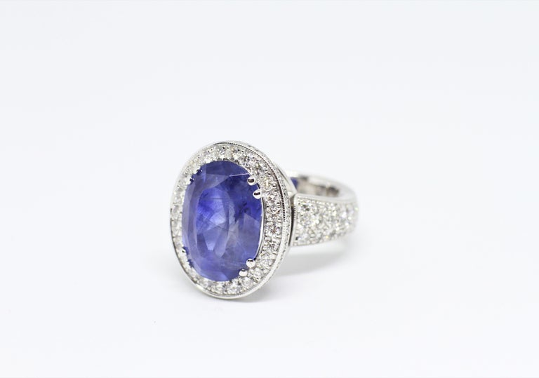 Beautiful cocktail ring featuring a natural unheated transparent blue oval sapphire in an 8 claw setting weighing an impressive 12.59 carats in the centre of a diamond halo cluster. The sapphire is surrounded by 24 round brilliant cut diamonds with