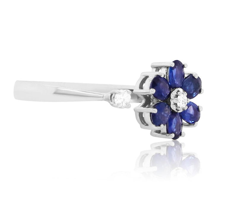 Material: 14k White Gold Gemstones: 6 Oval Blue Sapphires at 1.29 Carats - Measuring 3 x 4 mm Diamond Details: 2 Brilliant Round White Diamonds at 0.10 Carats. SI Clarity / H-I Color.   Fine one-of-a-kind craftsmanship meets incredible quality in