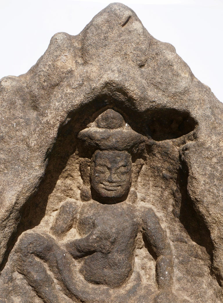 A large Cambodian Angkor Wat attributed sandstone stone fragment of an Apsara Buddha shrine with flame crown, 12th century.   Measures: Height 12 inches (30 cm) Width: 10 inches (25.5 cm)   Provenance: From a Canadian auction selling the estate