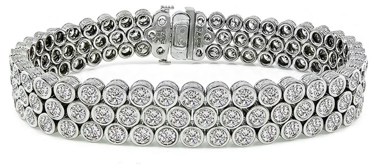 This 18k white gold bracelet by Jacobs & Co. is set with sparkling round cut diamonds that weigh 13.00ct. graded G color with VS clarity. The bracelet measures 7 inches in length and 11mm in width. The bracelet is stamped Jacobs & Co 13.00ct 18K 750
