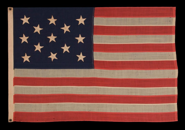 13 HAND SEWN STARS IN A 3-2-3-2-3 PATTERN ON A U.S. NAVY SMALL BOAT ENSIGN OF THE CENTENNIAL ERA, CIRCA 1870-1882:  Despite the fact that America hasn't been comprised of 13 states since 1791, 13 star flags have been made and displayed throughout