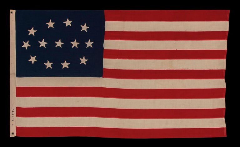 13 HAND-SEWN STARS IN AN ELLIPTICAL MEDALLION THAT FEATURES A ROW OF 3 STARS IN THE CENTER, A DESIGN IDENTIFIED ON JUST THREE SURVIVING FLAGS; CIVIL WAR - CENTENNIAL ERA (1861-1876)   13 star American national flag, made sometime in the period