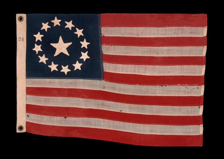 13 hand sewn stars in a circular version of what is known as the 3rd Maryland pattern, with an especially large center star, a flag with especially tiny scale among those with pieced-and-sewn construction, exceptionally rare, made circa 1890:  13