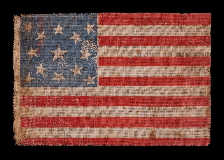 13 stars in a medallion pattern on an antique American parade flag, made for the 1876 centennial of American independence; an extremely scarce example with nice folk qualities