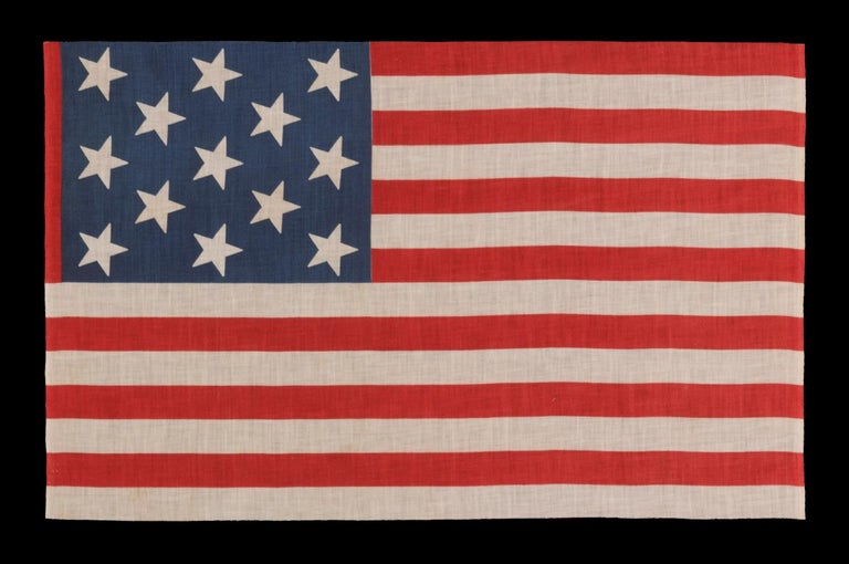 13 Star Parade Flag in a 3-2-3-2-3 Pattern, Made circa 1876-1898, Unusually Large and with an Unusual Star Pattern Among its Counterparts of the 19th Century.  13 star American national parade flag, printed on cotton, made sometime in the period