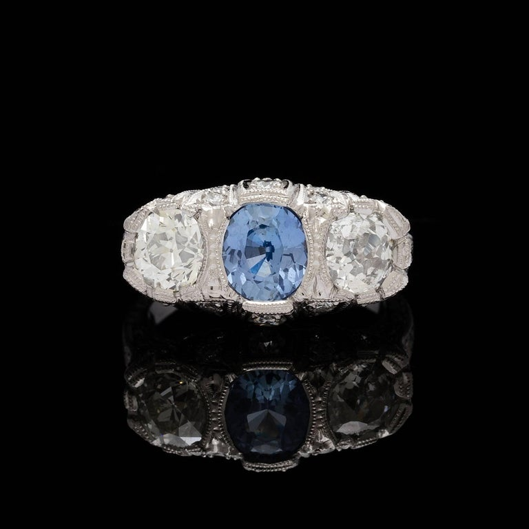 Platinum 3-stone filigree ring features a center GIA 1.30 carat oval cut unheated sapphire. The color is described as violetish blue, report # 1106710481 accompanies the sapphire. Set on each side of the sapphire are old european cut diamonds