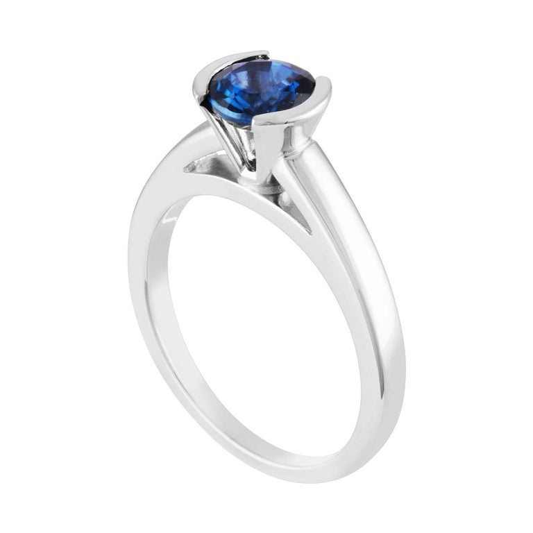 Solitaire Half Bezel Engagement Ring The ring is 14K White Gold The Blue Sapphire is a round 1.30 Carat Heated The ring is a size 7.00, sizable. The ring weighs 4.5 grams
