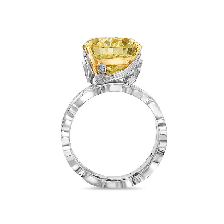 This engagement ring features a 13.11 carat fancy yellow VVS2 oval diamond set in a platinum and 18K yellow gold barouque style setting with matching band. GIA Certified. Report No. 5191115266. Size 8.   Resizeable upon request.  Viewings available