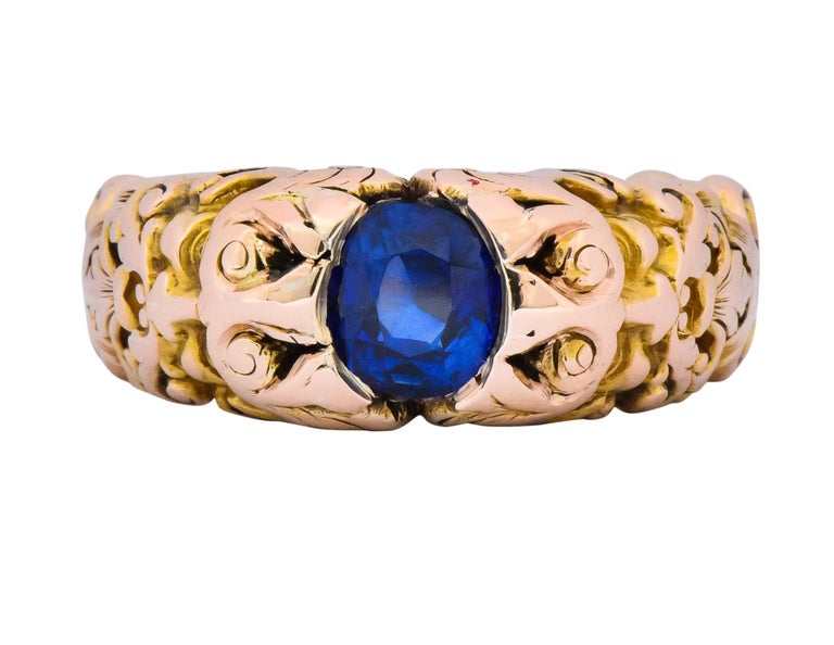 Centering an oval cut sapphire weighing 1.32 carats, bright blue with no evidence of heat treatment  Partial bezel setting  With incredibly detailed mount depicting Anemoi, the god of wind on both sides  Deeply engraved gold with pierced, scrolling