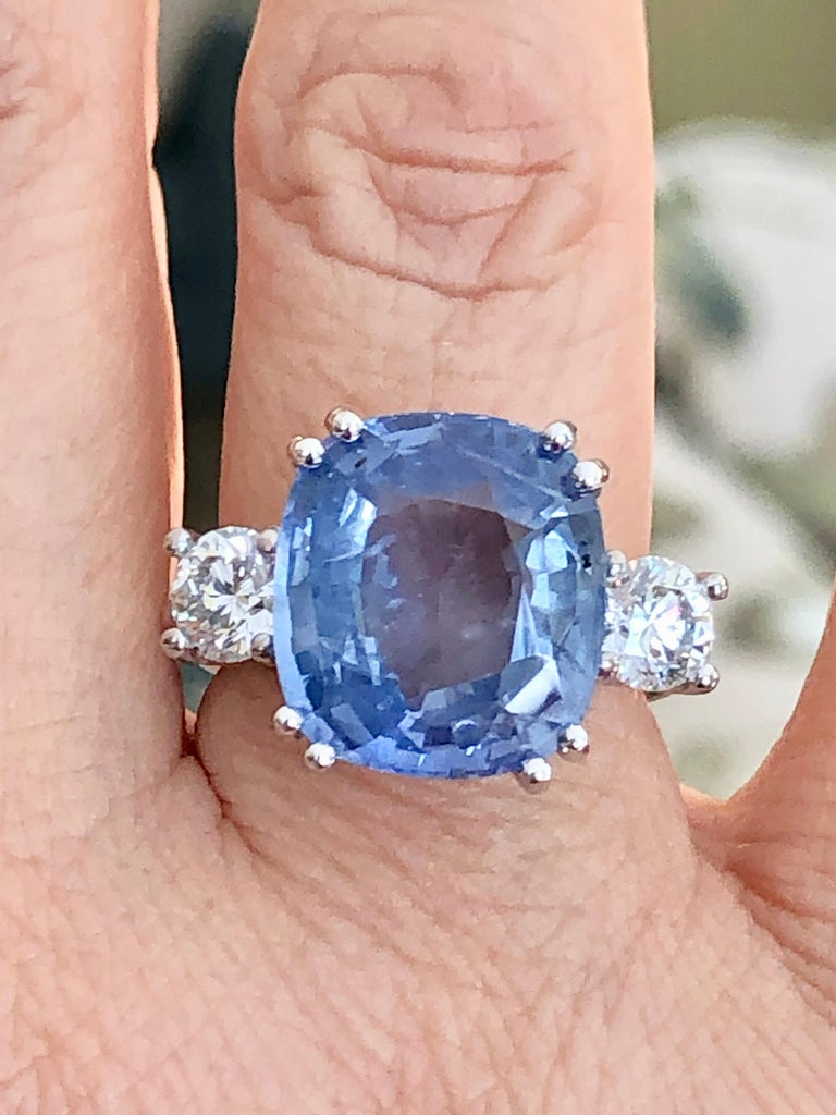 Spectacular 18K white gold sapphire and diamond engagement ring containing 1 cushion cut natural Ceylon blue sapphire with no heat treatment weighing 11.89 carats and 2 brilliant cut diamonds weighing 1.20 carats Measurements sapphire are 14.13 x