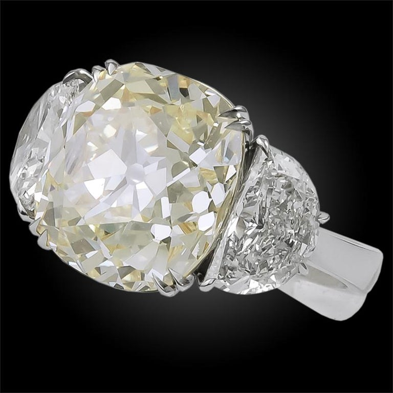 A magnificent natural fancy yellow old mine diamond, weighing approximately 13.23 carats with GIA cert, enveloped at each side by two exquisite half-moons shaped diamonds weighing approximately 3.31 carats, finely mounted in platinum gold. Ring size