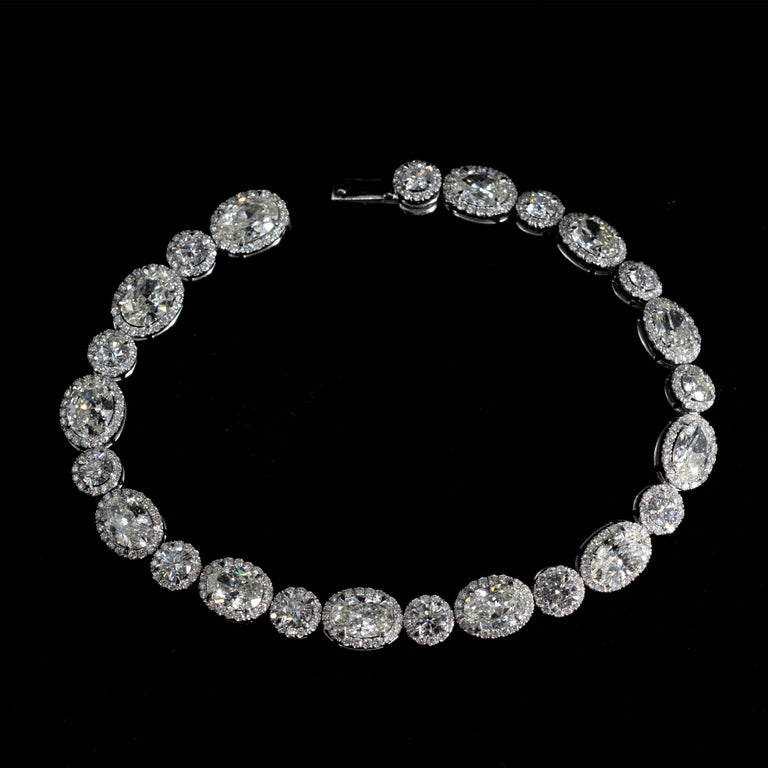 Exceptional 18 karat gold and diamond tennis bracelet: Twelve oval cut diamond about 0.75 carat each alternating with twelve round brilliant cut diamond each about 0.22 carat.  Each of these central stones are surrounded in a halo like pattern by