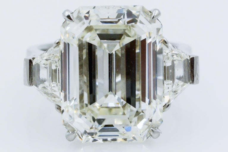 This 13.49ct emerald cut diamond has J color with VS1 clarity and is GIA certified. The diamond is flanked by two traps, weighing 1.80ctw with H color and VS1 clarity on a platinum band.