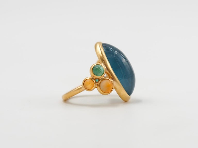 This delicate ring is composed of 7 stones: 1 large deep blue natural aquamarine cabochon of 13.5cts, 2 natural emerald cabochons and 4 cornaline cabochons.   The emeralds and aquamarines are natural stones with typical inclusions.   This