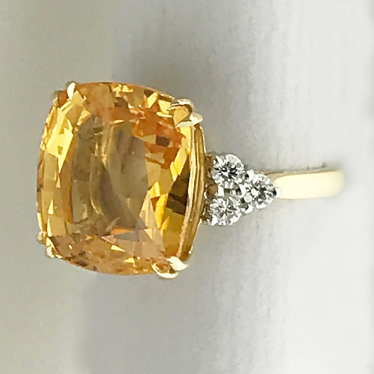 A rare natural colour, untreated, 13.55 carat cushion shape orange sapphire and diamond ring.  18ct yellow gold ring with three round brilliant diamonds on each shoulder G/H, Vs1-SI1, total weight approx 0.5ct.  Accompanied by GRS Gemresearch
