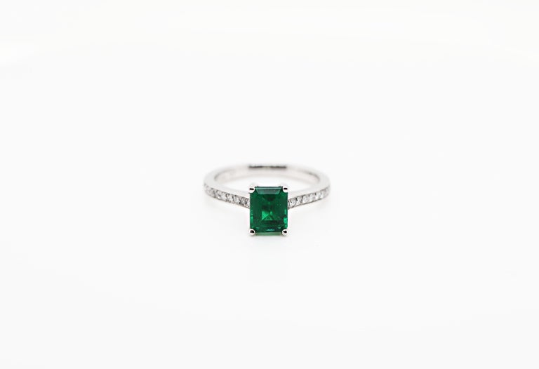 Engagement ring set with a vibrant emerald cut emerald weighing 1.36ct mounted in a four claw open back setting. The stone is beautifully accompanied by ten round brilliant cut diamonds pavé set on either shoulder weighing a total of 0.15ct set in