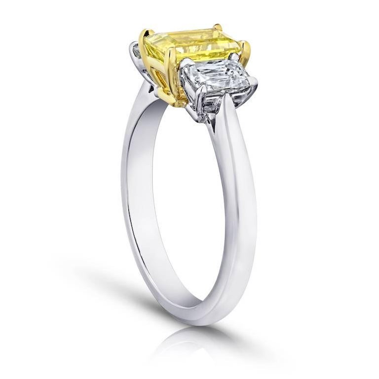 1.37 carat emerald cut (natural no heat) yellow sapphire set with two rectangular radiant cut  diamonds weighing .91 carats set in a platinum and 18k Yellow Gold Ring