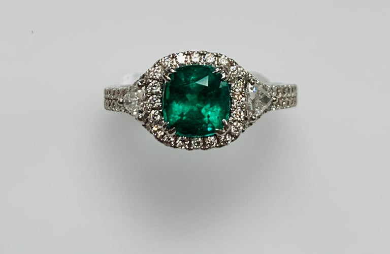 1.39 Carat cushion cut Columbian Emerald set in 18k white gold ring surrounded with 0.63 carat diamonds ,shield cut diamonds, and half way on the shank.