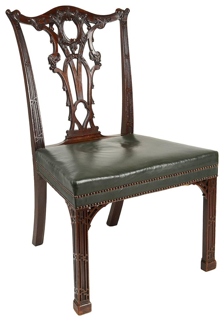 A fine quality set of 14 mahogany dining chairs in the Chippendale style (two later arms, 12 singles). Having carved scrolling foliate decoration to the backs, with gothic influenced blind fret work to the sides. Stuff over upholstered leather seats