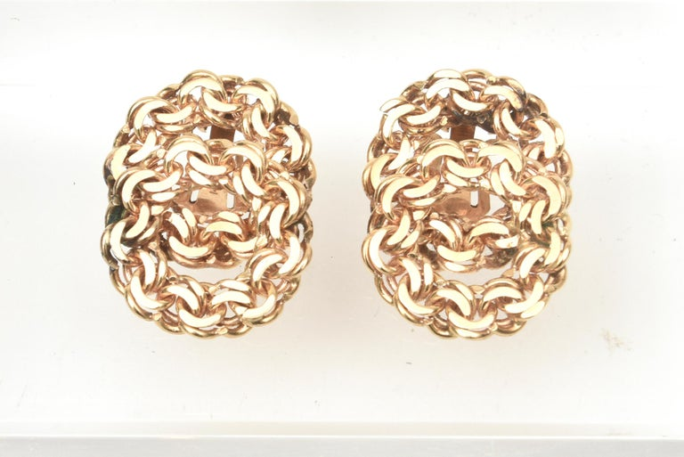 These lovely pair of 14K gold vintage clip on earrings are intertwined chains of gold. The lay flat on your lobe and are timeless. They are from the 50's and have a patent number just for the clip. Day to night season to season. They would look