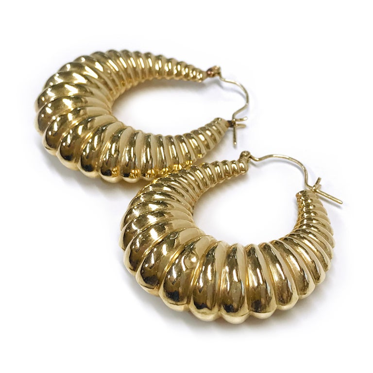 14 Karat Gold Hoop Doorknocker Earrings. These lightweight hollow shrimp hoops are the perfect accessory. Both earrings have small dents at the lower part of the earrings, see photos. The earrings have a hoop wire closure. The total gold weight of