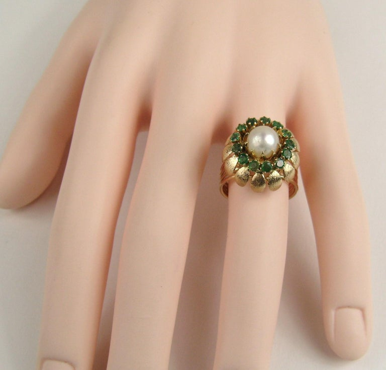 14K gold 1960s Cocktail ring. Very Mad Men! Center Pearl flanked with accent emerald stones. The ring sits up high (.50in) 4 ring open band with a flower motif setting. Ring is a size 7-1/4 and can be sized by us or your jeweler. Be sure to check