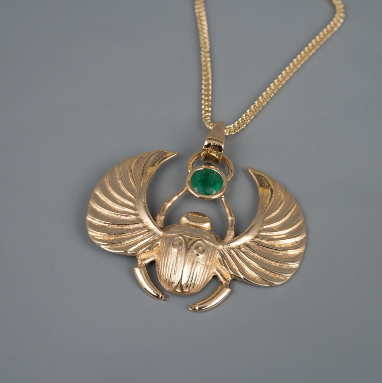 This Egyptian revival Winged Scarab Beetle pendant features a beautiful certified 0.41 carat round cut natural emerald gemstone.   The custom made his piece displays full UK hallmarks and is expertly modelled with textured detail to the body and