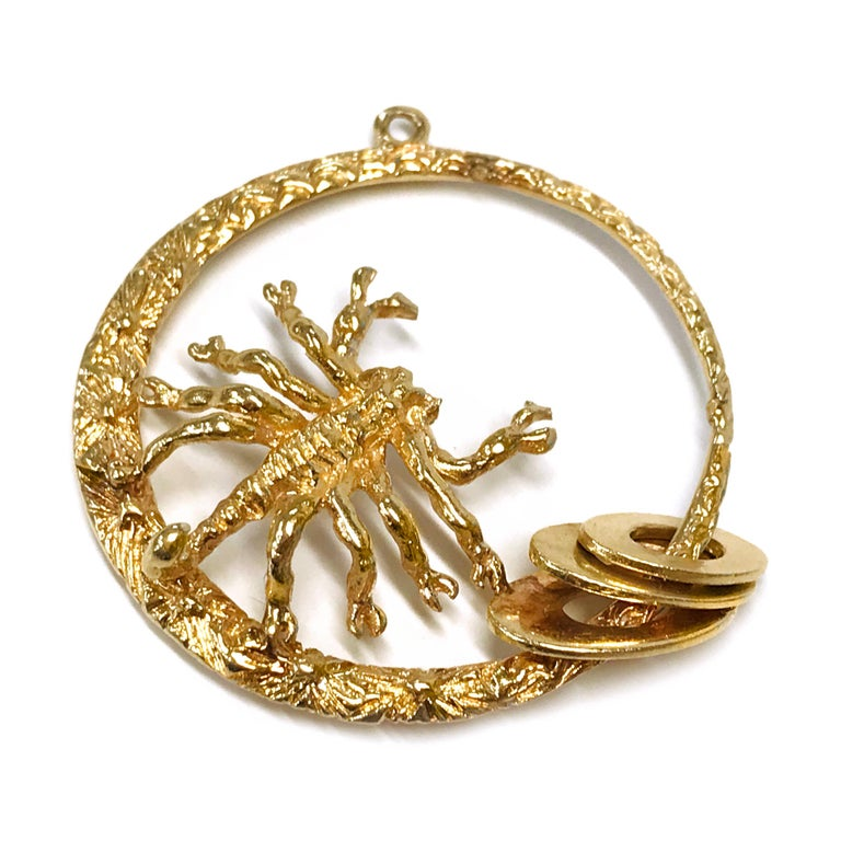 14 Karat Scorpion Pendant. The pendant measures 37.35mm in diameter. The pendant features a thin to wide circle with a scorpion that is facing the center of the pendant with three smooth oval discs near the bottom. The pendant circle is highly