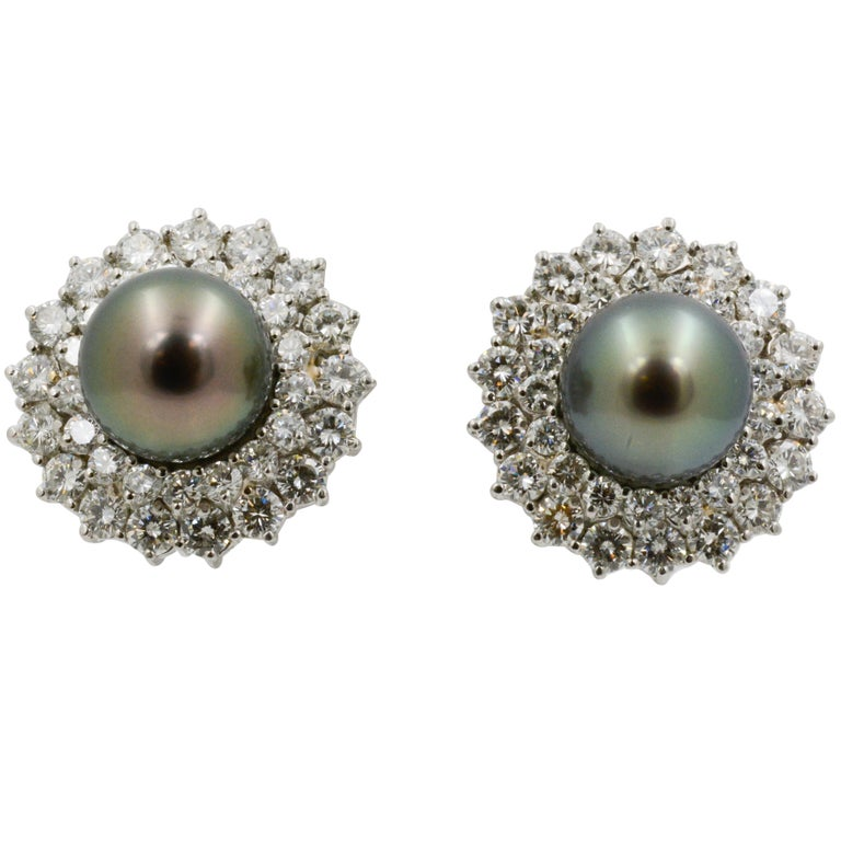 With a vintage inspired design, these 14k white gold and platinum clip back earrings have black pearls at the center that measures 12mm. The mesmerizing dark pearls are surrounded by two rows of 68 round diamonds, weighing a total of 5.00 carats